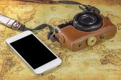 Smartphone y cámara de bolsillo en un mapa del mundo Fotos de archivo