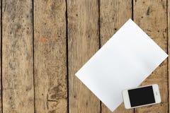 Smartphone y documento sobre la tabla de madera Foto de archivo
