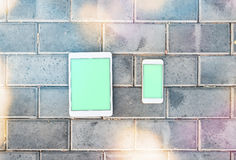 Smartphone y la maqueta hacen tabletas la PC contra una pared de ladrillo stock de ilustración