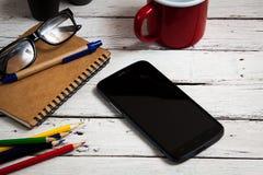 Smartphone y materiales de oficina en el tabel, visión superior Fotos de archivo
