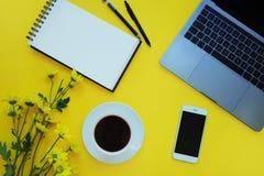 Smartphone y nota, flores, café, ordenador portátil en fondo amarillo Concepto de la oficina imágenes de archivo libres de regalías