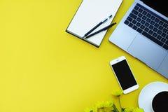 Smartphone y nota, flores, ordenador portátil del café en fondo amarillo Lugar para su texto imágenes de archivo libres de regalías