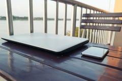 Smartphone y ordenador portátil en la madera de la tabla, delante de la opinión del río de la falta de definición Fotografía de archivo libre de regalías