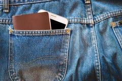 Smartphone y pasaporte blanco o cuaderno en blanco en sus tejanos del bolsillo Imagen de archivo libre de regalías