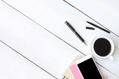Smartphone y pluma, cuaderno de la taza de café en el escritorio de madera blanco y fotografía de archivo