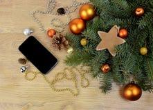 Smartphone y ramas de árbol en el fondo de madera Co moderno Imagen de archivo libre de regalías
