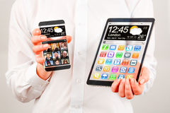 Smartphone y tableta con la pantalla transparente en manos humanas. Fotografía de archivo