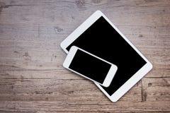Smartphone y una tableta en el fondo de madera Imagen de archivo libre de regalías