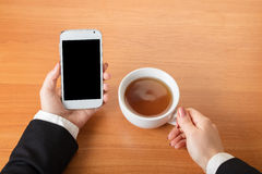 Smartphone y una taza de té imagenes de archivo