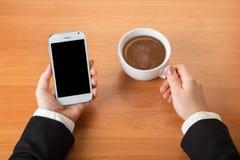 Smartphone y una taza de té fotos de archivo libres de regalías