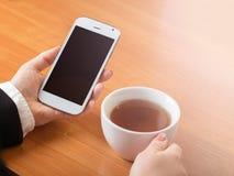 Smartphone y una taza de té fotografía de archivo libre de regalías