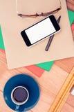 Smartphone y vidrios del ojo en el papel por la taza de café en la tabla Foto de archivo libre de regalías