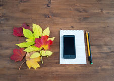 Smartphone, yellow leaves notebook and pencil Royalty Free Stock Photos