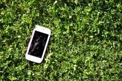 Smartphone z łamanym parawanowym lying on the beach na trawie Obrazy Royalty Free