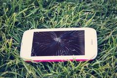 Smartphone z łamanym parawanowym lying on the beach na trawie Zdjęcie Royalty Free