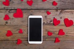 Smartphone z czerwonym sercem na drewno stole Fotografia Royalty Free