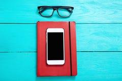 Smartphone z kopia notatnikiem blisko szkieł na błękitnym drewnianym stole i przestrzenią Odgórny widok up i egzamin próbny kosmo zdjęcia stock