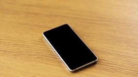 Smartphone z pustym czerń ekranem na drewnianym stole zdjęcie wideo
