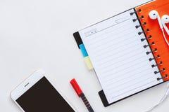 Smartphone z rozpieczętowanym ślimakowatym notatnikiem, piórem i słuchawkami na whi, fotografia stock