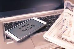 Smartphone z Sfałszowanymi wiadomości słowami na ekranie nad gazetą i laptopem Sfałszowana wiadomość, bajerowania pojęcie fotografia stock