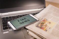 Smartphone z Sfałszowanymi wiadomości słowami na ekranie nad gazetą i laptopem Sfałszowana wiadomość, bajerowania pojęcie obraz royalty free