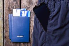 Smartphone in zak van broeken en paspoorten Stock Foto