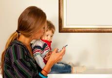 Smartphonemededeling van de moederbaby stock afbeeldingen