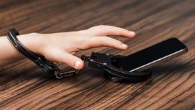 Smartphonen handfängslas i handen av lite pojken en symb royaltyfria foton