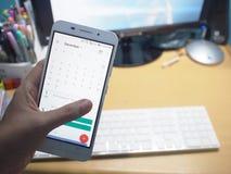 Smartphonen med det arbetande skrivbordet arkivfoto