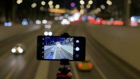 Smartphonen monteras på en tripod De skjuter på videoen, trafik av bilar, mot en bakgrund av härliga ljus lager videofilmer