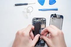 Smartphonen var skador och behov för att reparera som bearbetar smartphonen, som står på vit bakgrund fotografering för bildbyråer