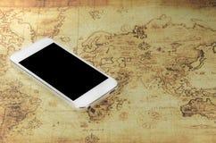Smartphoneon un mapa del mundo Fotos de archivo libres de regalías