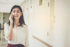Smartphones asiáticos do uso dos homens de negócios das mulheres para contactar o trabalho e o busi foto de stock