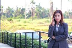 Smartphones asiáticos do uso dos homens de negócios das mulheres para contactar o trabalho e o busi fotografia de stock royalty free