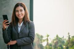 Smartphones asiáticos do uso dos homens de negócios das mulheres para contactar o trabalho e o busi fotos de stock