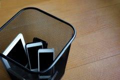Smartphones in bidone della spazzatura Fotografia Stock