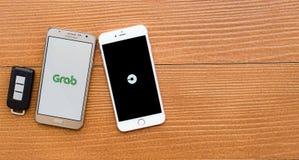 2 smartphones che mostrano applicazione della GRU A BENNA e di UBER fotografia stock libera da diritti