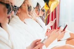 Smartphones de peignoirs de relaxation de femmes de station thermale de loisirs images libres de droits