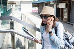 Smartphones do uso do viajante da mulher e guardar um mapa para o curso do achado imagens de stock royalty free