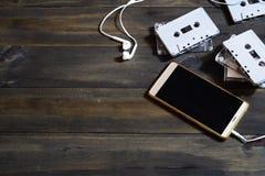Smartphones e cassetes de banda magnética no fundo de madeira Conceito moderno e retro do fundo das tecnologias Vista superior co foto de stock royalty free