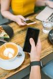 Smartphones en manos con el reloj elegante con café y el ordenador portátil Fotos de archivo libres de regalías