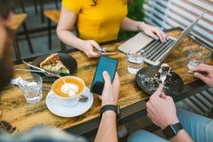 Smartphones i händer över tabellen med kaffe och bärbara datorn Fotografering för Bildbyråer