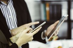Smartphones och minnestavlor f?r aff?rsman- och aff?rskvinnabruk som ?r f?rest?ende med begreppet av bekv?mlighet i shopping dire arkivfoton