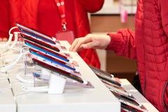 Smartphones på räknaren av ett elektroniklager, säljaren hjälper köparen att välja en produkt arkivfoton