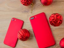 Two red phones and Christmas balls. Smartphones of red color lie on a wooden table next to Christmas balls Royalty Free Stock Photos