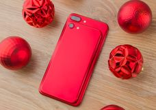 Two red phones and Christmas balls. Smartphones of red color lie on a wooden table next to Christmas balls Royalty Free Stock Images