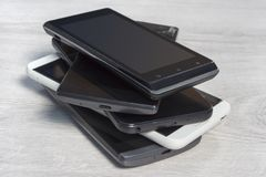 Smartphones stacked on top of each other are on the counter. Smartphones stacked on top of each other are on the counter stock image