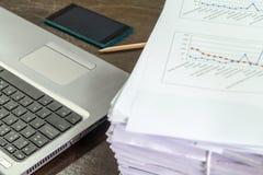 Smartphones sur l'ordinateur portable près de la pile documents Image libre de droits