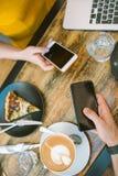 Smartphones w rękach nad stołem z kawą i laptopem Zdjęcie Stock