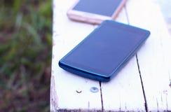 Smartphones zapominający na ławce zdjęcie royalty free